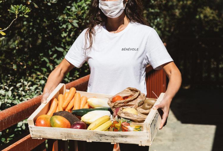 Bénévole portant un panier de légumes pendant la crise du coronavirus