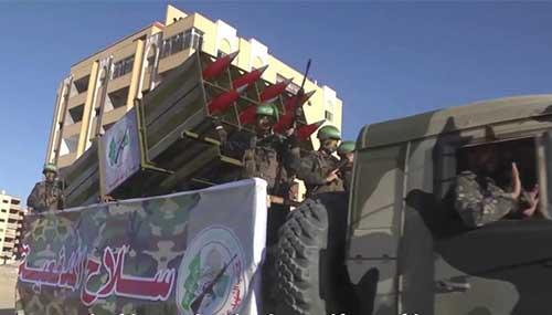 Défilé de combattants du Hamas (bandeau vert) avec un lance-roquettes chargé de missiles